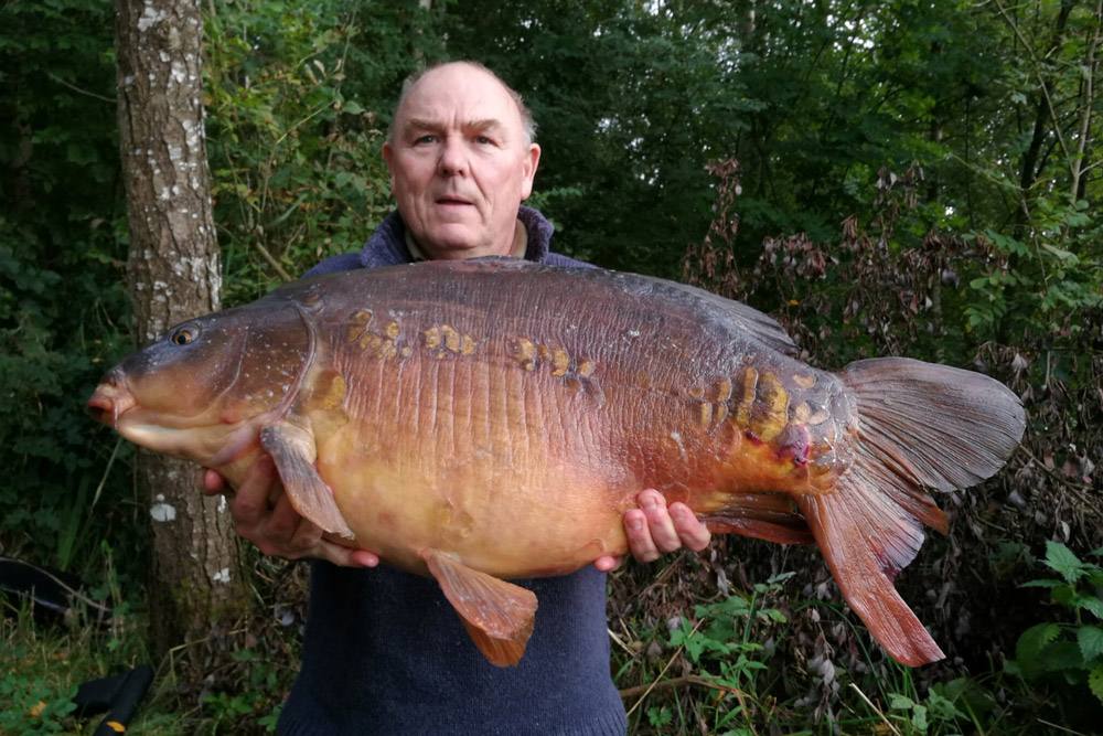 Paul McBride with a large mirror carp caught from Loughgall